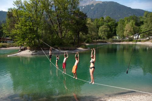 5 Personen stehen auf einer Waterline über einem See mit Halteseil